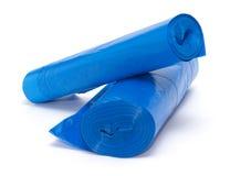 Rulle av blåa plast- avskrädepåsar som isoleras på vit Royaltyfri Bild