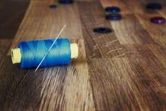 Rulle av den blåa sömnadtråden med en visare och knappar på träbakgrund Royaltyfria Bilder