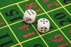 Rulle av den vita tärningen på den modiga tabellen i en kasino Arkivfoton