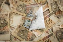 Rulle av dollarräkningar och kokain överst av 50 reaisanmärkningar Arkivbild