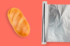 Rulle av försilvrar folie på pappröret nära nytt ovalt wheaten bröd lägger på tabellen som bor korallfärg på kök Lekmanna- lägenh arkivbild