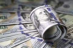 Rulle av hundra oss dollarräkningar på bakgrund för dollarräkningar Arkivfoton