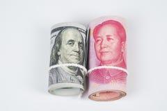 Rulle av hundra US dollarräkningar och kinesiska yuansedlar w arkivbilder