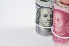 Rulle av hundra US dollarräkningar och kinesiska yuansedlar w royaltyfria foton