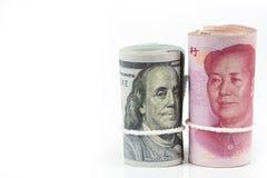 Rulle av hundra US dollarräkningar och kinesiska yuansedlar w royaltyfri foto