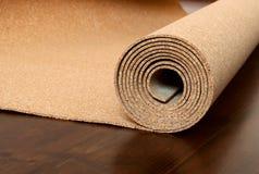 Rulle av kork ligger på ett brunt golv Arkivbild