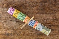 Rulle av olika eurosedelpengar med den guld- bandpilbågen på Royaltyfri Fotografi