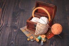 Rulle av tråden, fingerborg och en ask med handarbete arkivfoton