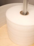 Rulle av vitt industriellt skum för förpacka på en rullutmatare Arkivbild