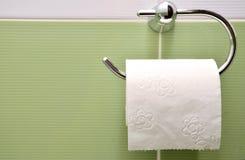 Rulle av vitt toalettpapper på metallpappershållare Royaltyfri Fotografi