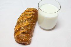 Rulle, bakelse och exponeringsglas av mjölkar isolerat på vit bakgrund Royaltyfria Foton