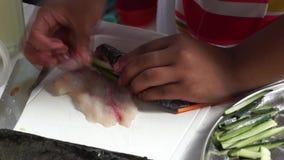 Rulle för sushi för fisk för grundskolaflickastoppning, som hon konkurrerar i årlig laga mat konkurrens stock video