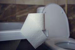 Rulle för toalettpapper på kanten av badet På bakgrunden av toaletten Royaltyfria Bilder
