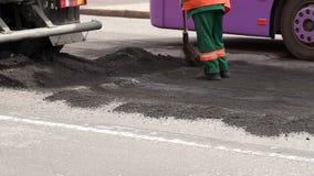 Rulle och arbetare p? att asfaltera och reparation av stadsgator N?rbild arkivfilmer