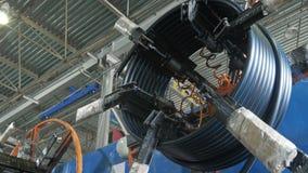 Rulle som dragar spoleröret Tillverkning av den plast- fabriken för vattenrör Process av plast- rör för danande på maskinen Arkivfoto