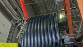 Rulle som dragar spoleröret Tillverkning av den plast- fabriken för vattenrör Process av plast- rör för danande på maskinen Royaltyfri Bild