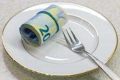 Rullen som består av 20 euro pengar samman med en gaffel, är lögnen på en vit platta Arkivfoto