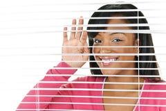 rullgardiner som ser den le kvinnan arkivfoto
