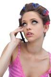Rulli d'uso dei capelli del giovane modello premuroso con il telefono Fotografia Stock