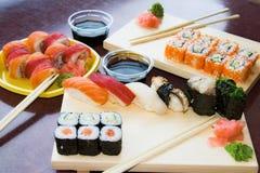 Rulli di sushi con salsa sulle zolle Fotografie Stock Libere da Diritti