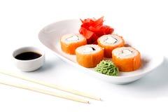 Rulli di sushi squisiti sulla zolla bianca con le bacchette e il wasabi Fotografia Stock Libera da Diritti
