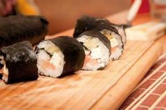Rulli di sushi sulla scheda di legno Fotografia Stock