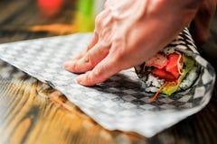 Rullning av en sushiburrito med rutigt papper Arkivfoto