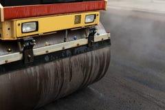 Rullo compressore che appiattisce nuovo asfalto Immagini Stock