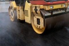 Rullo compressore che appiattisce nuovo asfalto Fotografie Stock