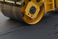 Rullo compressore che appiattisce nuovo asfalto Immagine Stock