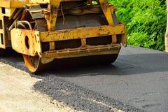 Rullo compressore che pone asfalto fresco immagine stock