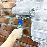 Rullo di pittura tramite un muro di mattoni immagine stock libera da diritti