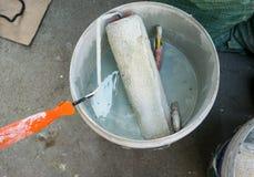 Rullo di pittura utilizzato e spazzola di pittura inzuppata nel buc di plastica di colore Immagine Stock