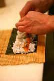 Rullo di sushi di rotolamento del cuoco unico Immagine Stock