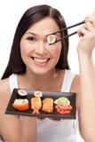 Rullo di sushi sorridente della holding della donna con bacchette Immagini Stock