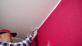Rullo di vernice con i campioni della vernice Un uomo in un cappello rosso che colora una stanza con un pennello del rullo di pit archivi video