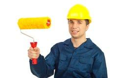 Rullo di vernice sorridente della holding dell'uomo dell'operaio fotografie stock libere da diritti