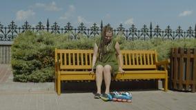 Rullo femminile che mette sulle scarpe che si siedono sul banco video d archivio