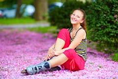 Rullo-pattinatore sveglio della ragazza nel parco di primavera Immagini Stock