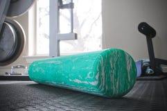Rullo verde della schiuma di allenamento sul pavimento della palestra Fotografie Stock Libere da Diritti