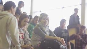 Rullskateboradåkare, åhörare sitter på språngbrädor på konkurrens i skatepark Flickablick in camera arkivfilmer
