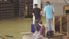 Rullskateboradåkare blir på språngbrädor som förbereder sig, utför på konkurrens i skatepark strid lager videofilmer