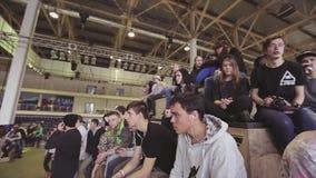 Rullskateboradåkare och åhörare håller ögonen på konkurrens i skatepark hörlurar challenge ungdom stock video