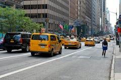 Rullskateboradåkare- och taxitaxiar, 5th ave, New York Arkivbild