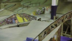 Rullskateboradåkaren gör 360 flip, hastigt greppfot i luft Extrem flip på språngbrädan Konkurrens i skatepark lager videofilmer