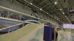 Rullskateboradåkaren gör flip i luft, hastigt greppfot i hand Extremt jippo Konkurrens i skatepark arkivfilmer