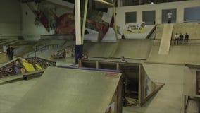 Rullskateboradåkaren gör flip 360 i luft språngbräda extremt trick Konkurrens i skatepark arkivfilmer