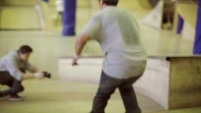 Rullskateboradåkaren gör flip 360, innan han hoppar på språngbrädan Extremt jippo Konkurrens i skatepark arkivfilmer
