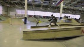 Rullskateboradåkaren gör mislyckad plugghäst på språngbrädan extremt trick Konkurrens i skatepark stock video