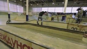 Rullskateboradåkaren gör plugghäst på språngbrädan, hopp extremt trick Konkurrens i skatepark trick arkivfilmer